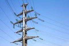 高压输电线灰色金属支柱有许多在清楚的无云的蓝天的导线垂直的视图 免版税库存照片