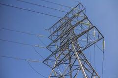 高压输电线的钢定向塔反对蓝天 库存照片