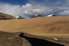 高地路:涂柏油黑腰带级选手路到在黄色小山中的前面在山背景高多雪的山峰,蓝色sk 免版税库存照片