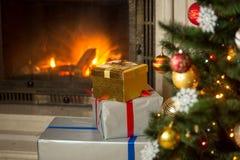 高堆在房子的圣诞节礼物有灼烧的壁炉的 图库摄影
