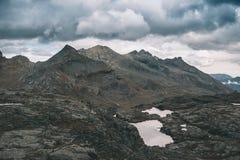 高处岩石风景和一点湖 与剧烈的风雨如磐的天空的庄严高山风景 广角看法从上面,吨 库存照片