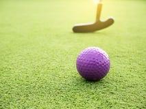 高尔夫俱乐部和球在草和日落 免版税库存图片