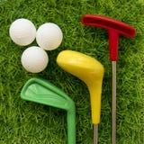 高尔夫俱乐部和球孩子的绿草的 免版税库存照片