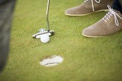 高尔夫球、轻击棒和男孩的腿在绿色 库存照片