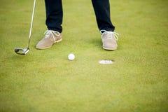 高尔夫球、轻击棒和男孩的腿在绿色 免版税库存图片