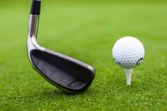 高尔夫球发球区域在绿草路线的球俱乐部司机 免版税库存图片