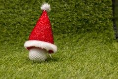 高尔夫球和圣诞老人帽子在绿草 库存照片