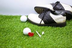 高尔夫球和鞋子在绿草 库存照片