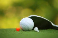 高尔夫球和高尔夫俱乐部在有阳光的晚上高尔夫球场 库存照片