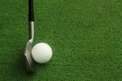 高尔夫球和高尔夫俱乐部在绿草 免版税库存图片