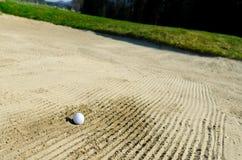 高尔夫球在沙子地堡被困住 库存照片