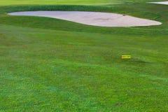 高尔夫球地堡和一个定向标志高尔夫车的 图库摄影