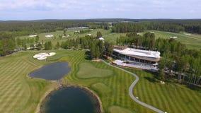 高尔夫球场在一个晴天,与池塘的一家优秀高尔夫俱乐部和绿草,从天空的看法 免版税库存图片