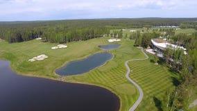 高尔夫球场在一个晴天,与池塘的一家优秀高尔夫俱乐部和绿草,从天空的看法 免版税库存照片