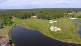 高尔夫球场在一个晴天,与池塘的一家优秀高尔夫俱乐部和绿草,从天空的看法 库存图片