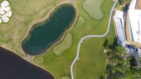 高尔夫球场在一个晴天,与池塘的一家优秀高尔夫俱乐部和绿草,从天空的看法 免版税图库摄影