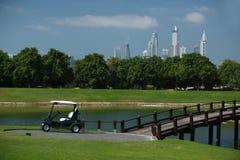 高尔夫球场在有棕榈树和摩天大楼的迪拜在背景中 免版税库存照片