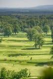 高尔夫球场有华美的绿色和意想不到的山景 免版税库存照片