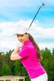 高尔夫球场的女孩有高尔夫俱乐部的 库存图片