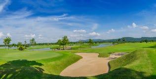 高尔夫球场绿色在场面背景的蓝色云彩天空下 库存照片