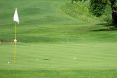高尔夫球场,打高尔夫球与旗子的绿色在孔 库存图片