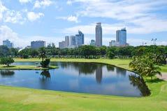 高尔夫球场绿色有城市背景 免版税库存图片