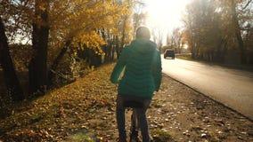 高尔夫球外套乘驾的少女在太阳骑自行车,在一条柏油路的边,在秋天公园,反对背景  影视素材