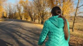 高尔夫球外套乘驾的少女在路骑自行车在秋天公园,以黄色树为背景 股票视频