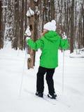 高尔夫球外套滑雪的照片女孩在冬天森林里 库存照片