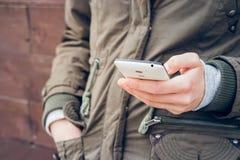 高尔夫球外套的女孩在一只手上的拿着一个智能手机 免版税库存照片