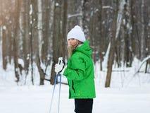 高尔夫球外套的女孩在阳光下在滑雪的冬天森林 库存照片