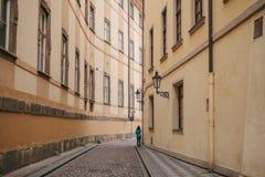 高尔夫球外套的旅游女孩沿美丽的离开的狭窄的街道走在布拉格在两个历史建筑之间 免版税库存图片