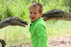 高尔夫球外套的男孩由两个恐龙头塑造 库存照片