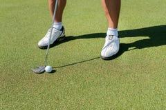 高尔夫球天 的高尔夫球运动员拿着俱乐部和击中去 免版税库存图片