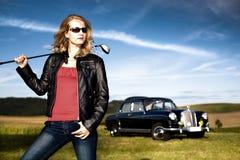 高尔夫球女孩和一辆经典汽车 免版税库存图片