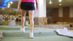 高尔夫球微型使用 打微型高尔夫球的年轻女人户内 来离球较近 影视素材