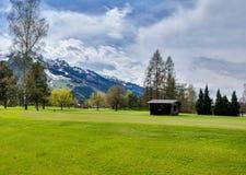 高尔夫球手段全景与村庄的 免版税库存照片