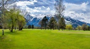 高尔夫球手段全景与村庄的 免版税库存图片