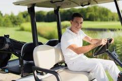 高尔夫球比赛的时刻  一套白色衣服的一个人乘坐一辆白色高尔夫车 免版税库存图片
