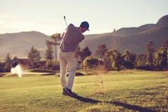 高尔夫球球击人 免版税库存照片