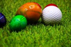 高尔夫球用在绿草的复活节彩蛋 库存图片