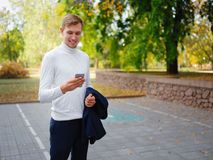 高尔夫球的一个人在他的手上拿着一件夹克并且传送在电话的信息 外面 免版税图库摄影