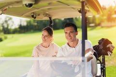高尔夫球的一了不起的天 夫妇在一辆白色高尔夫车坐 在树干说谎与高尔夫俱乐部的一个袋子 免版税库存照片