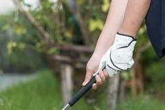 高尔夫球运动员佩带的白色手套holdiing的高尔夫俱乐部 免版税库存图片