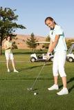 高尔夫球运动员俏丽的妇女 免版税库存图片