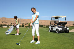 高尔夫球运动员俏丽的妇女 免版税图库摄影