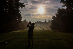 高尔夫球运动员剪影在黎明 库存图片