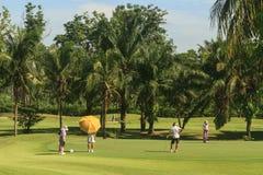 高尔夫球运动员和小型运车在高尔夫球场在泰国 库存图片