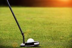 高尔夫球运动员在晚上高尔夫球场投入高尔夫球 免版税库存照片