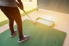 高尔夫球运动员妇女的腿实践在绿色路线的高尔夫球的 免版税库存照片